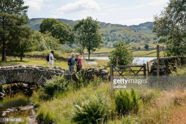 three senior men take picture whilst crossing bridge. - english lake district stock pictures, royalty-free photos & images