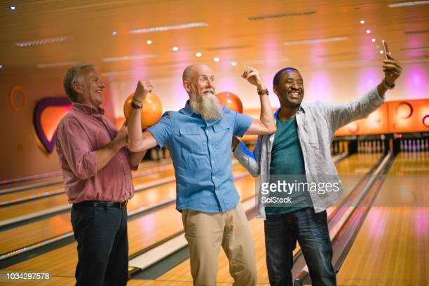 drie senior mannen bowlen - alleen seniore mannen stockfoto's en -beelden