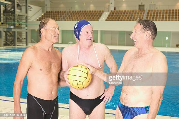 three senior men wearing swimwear, holding football at poolside - old man in speedo stock photos and pictures