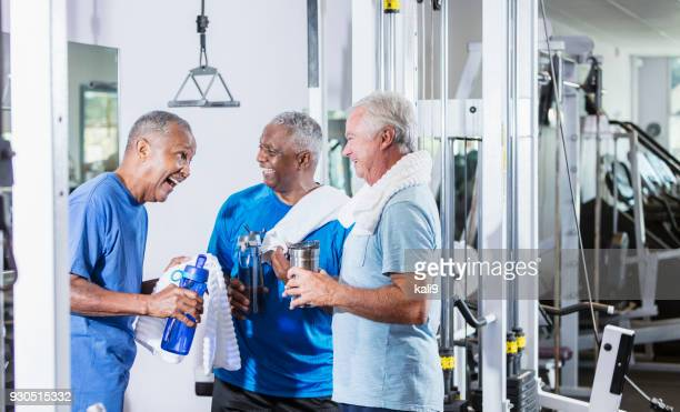 Three senior multi-ethnic men working out at gym talking