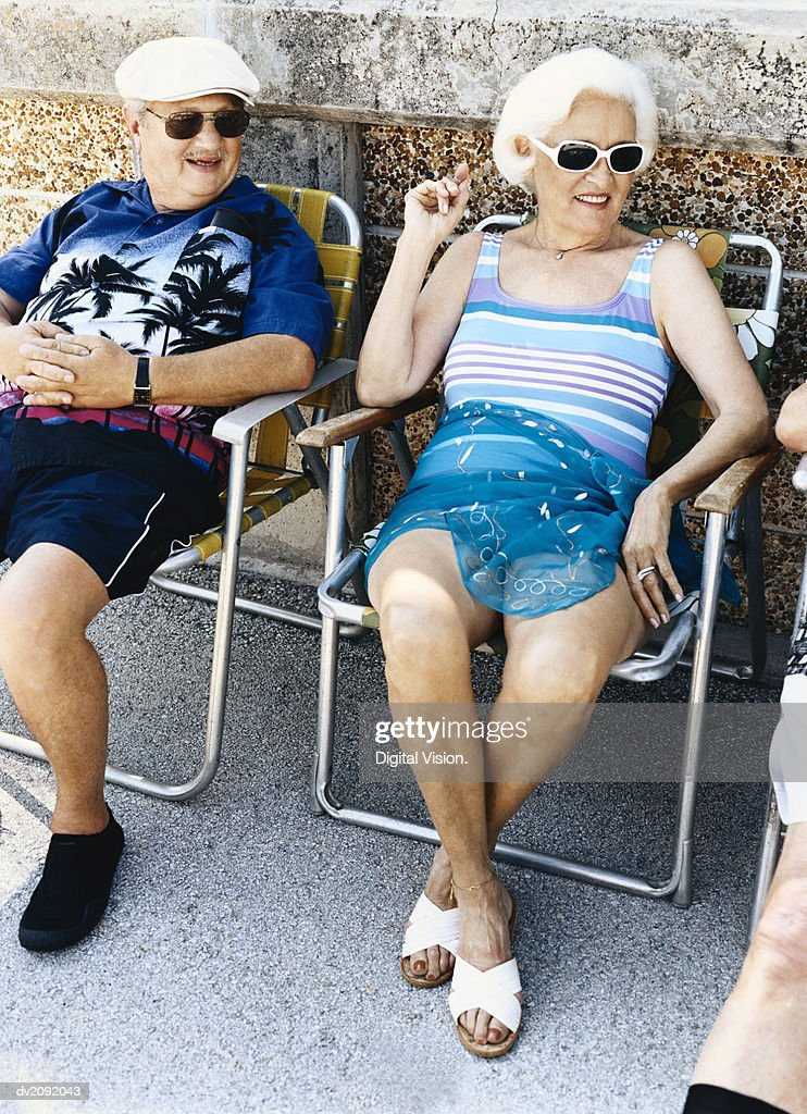 Three Senior People Sitting on Chairs in the Sun : Stock Photo