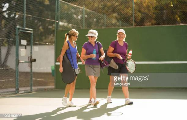 three senior women arriving at tennis court for practice. - tennis stock pictures, royalty-free photos & images