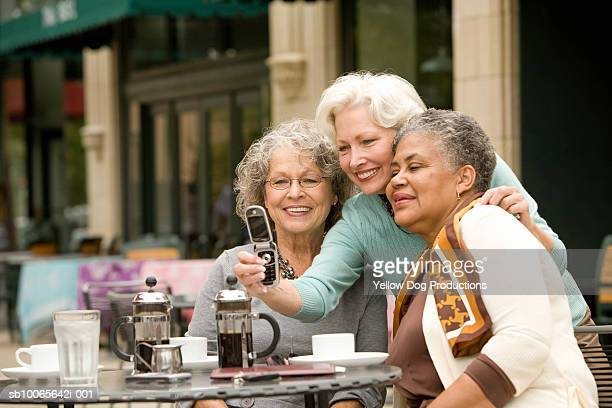 Three senior women at cafe taking self-portrait photograph with mobile phone