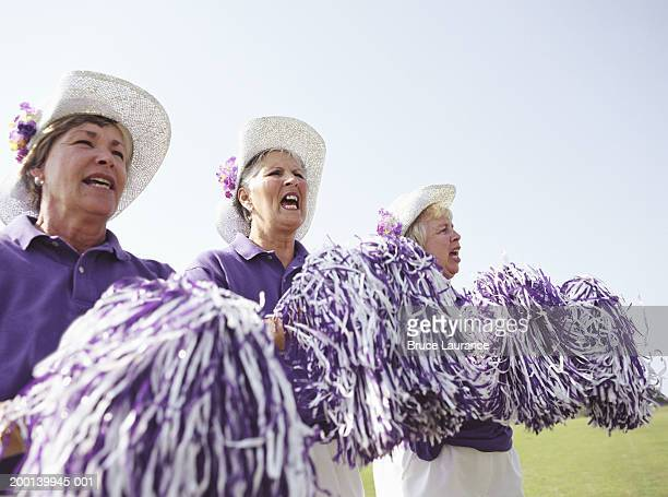 Three senior women in cheerleading uniforms cheering