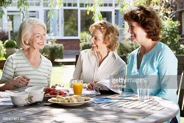 three senior women in garden looking at holiday brochures, smiling - 隣り合わせ ストックフォトと画像