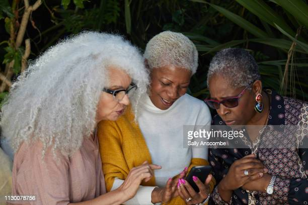 Three Senior Women in the garden using a smart phone