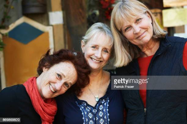 three senior women lean on each others' shoulders and smile at camera - midwest usa stock pictures, royalty-free photos & images