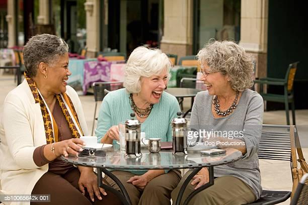 Three senior women sitting at cafe table, laughing