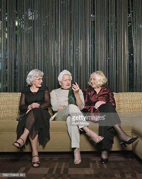 Three senior women sitting on sofa, looking at cell phone