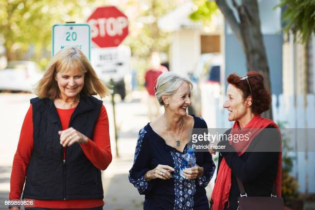 three senior women walk down the street and talk - small town stock pictures, royalty-free photos & images