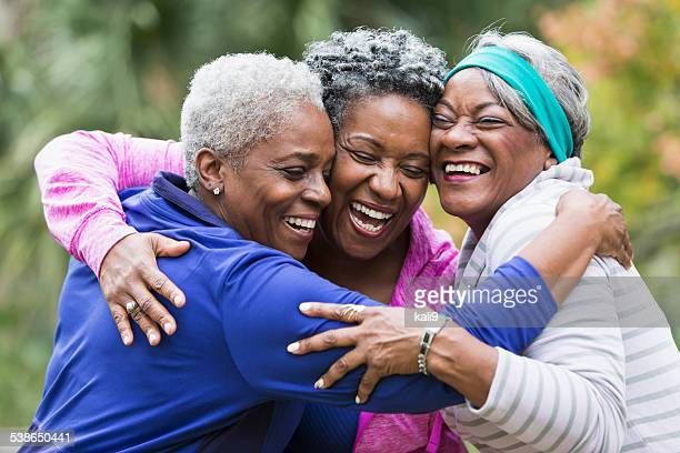 Three seniors hugging