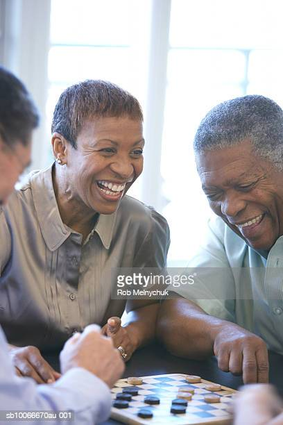 Three seniors playing checkers, indoors