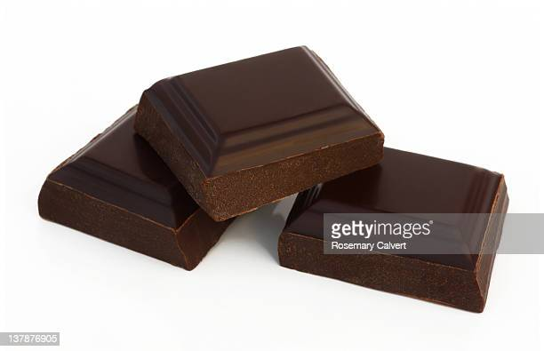 Three separate squares of organic dark chocolate.