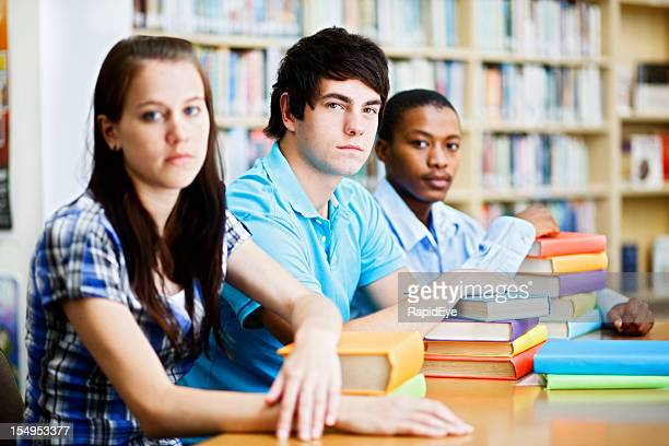 Three serious students sitting at library table