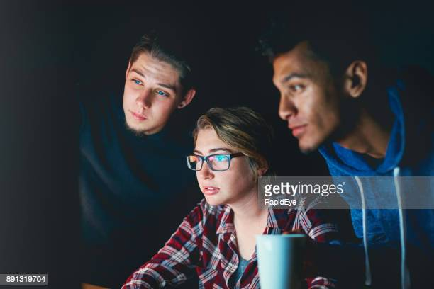 Three serious young people study computer monitor at night