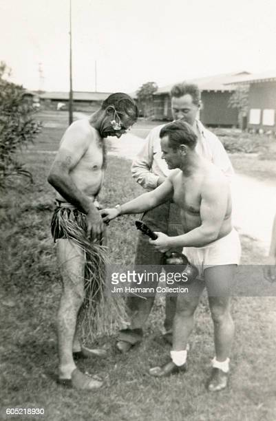 Three servicemen standing outdoors in their underwear One is wearing a hula skirt One holds a musical instrument