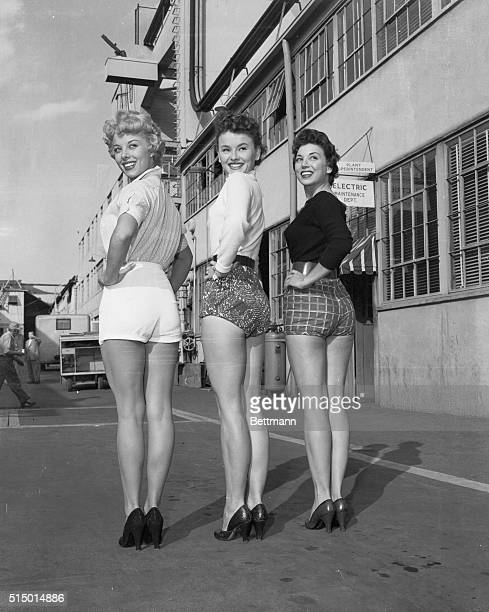 Three shapely but indignant Columbia starlets pause to pose for photographers as they paraded their legs around the studio lot yesterday to show...
