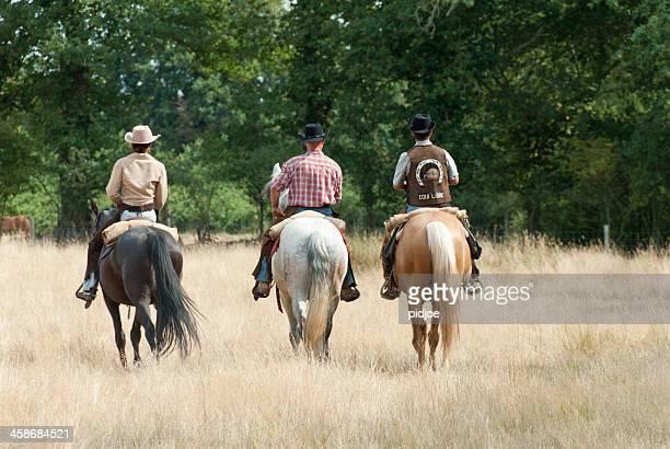 three shepherds riding horseback herding sheep
