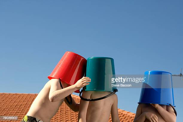 Three shirtless boys (6-7, 8-9)  with buckets on heads standing in garden