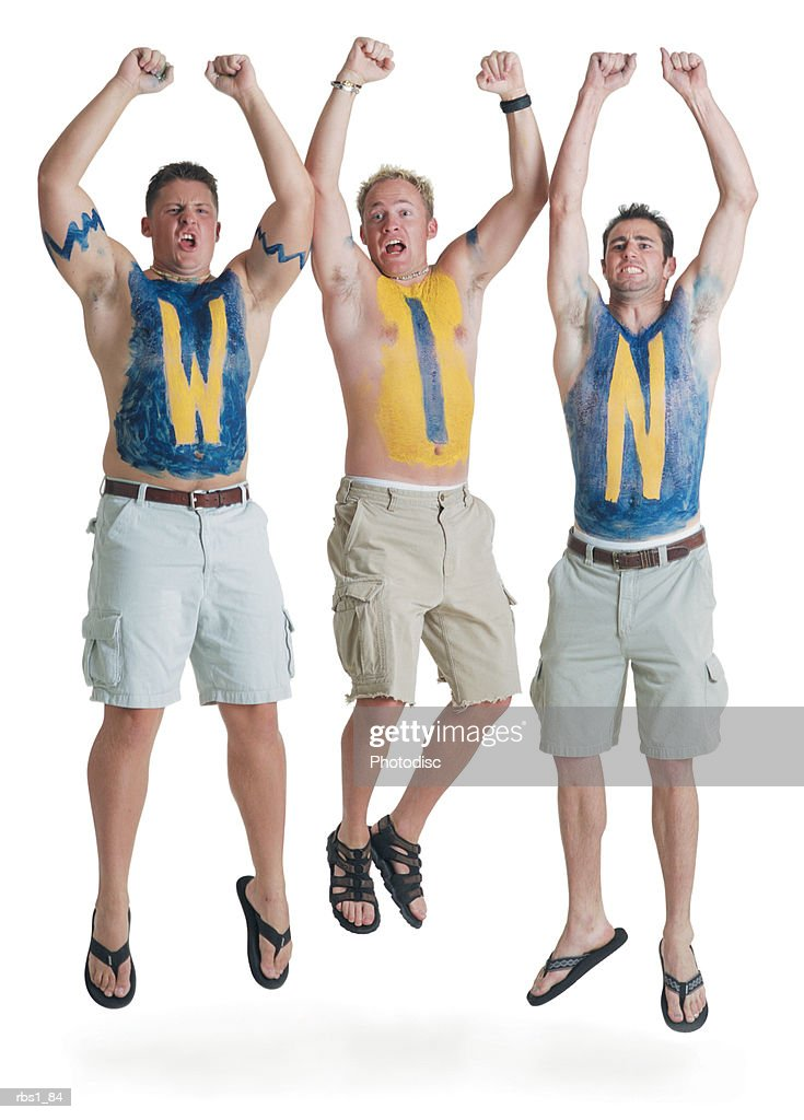 three shirtless caucasian male super fans with the letters w i n painted on their chests jump in the air in celebration : Foto de stock