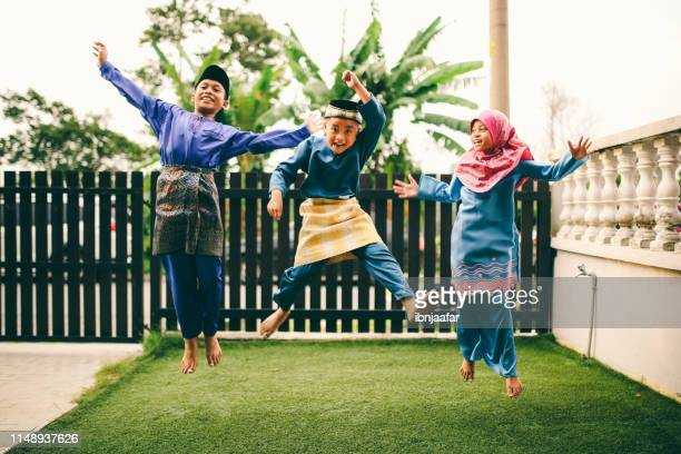 three sibling playing in front of house - eid al adha stock pictures, royalty-free photos & images