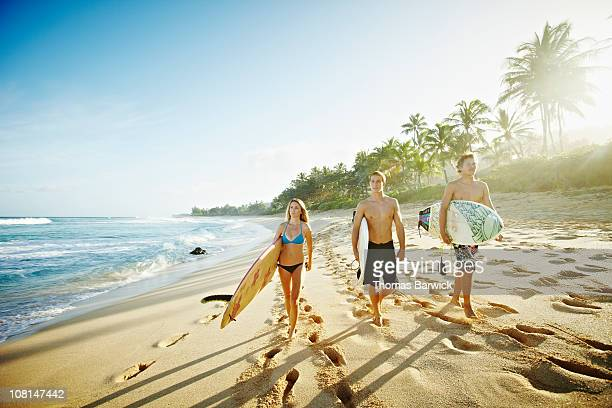 Three siblings carrying surfboards down beach