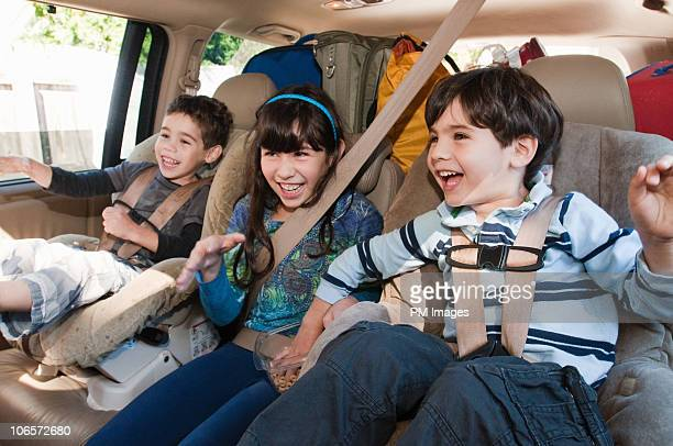 Three siblings in back seat of car