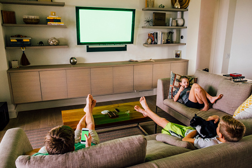 Three Siblings on Living Room Sofa with Green Screen TV in Background - gettyimageskorea