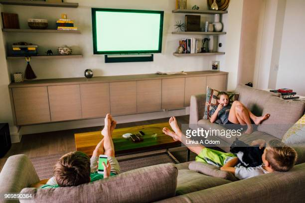 Three Siblings on Living Room Sofa with Green Screen TV in Background