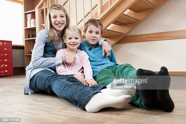 three siblings - girls in socks stock photos and pictures
