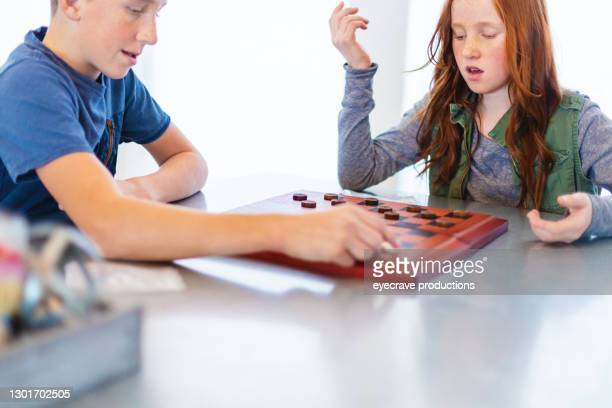 three siblings playing checkers together at dining table photo series - chequers stock pictures, royalty-free photos & images