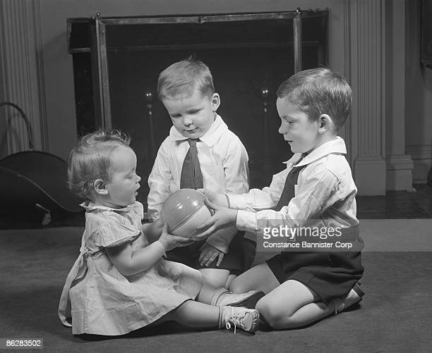Three siblings playing with ball in living room