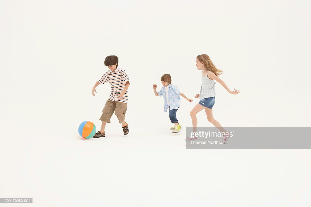 Three siblings (7-11) playing with beach ball : Foto de stock