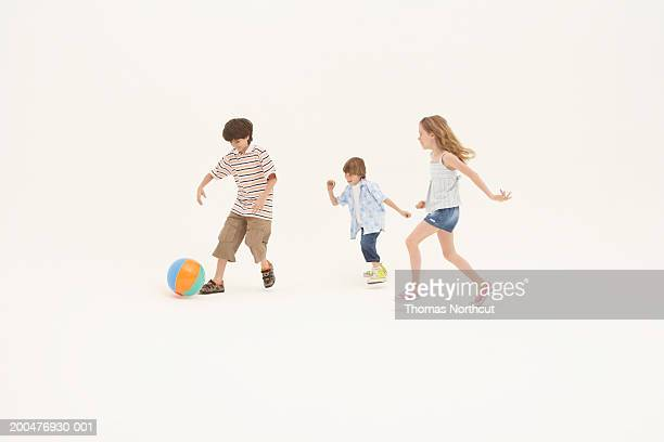 Three siblings (7-11) playing with beach ball