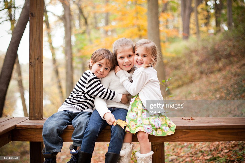 Three siblings posing for a picture in an Autumn forest : Stock Photo