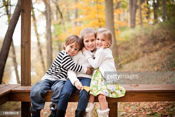 Three siblings posing for a picture in an Autumn forest