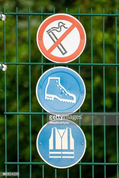 Three signs for occupational safety are fastened to a fence
