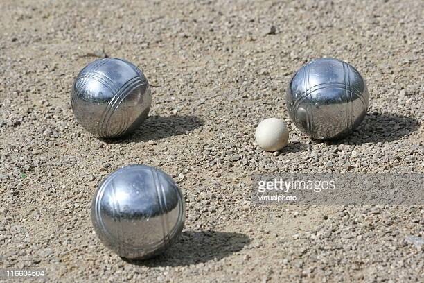 Three silver petanque on the ground