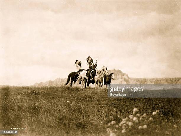 Three Sioux Indians of horseback on plains with rock formation in background.