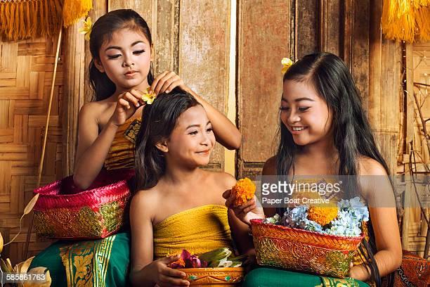 Three sisters at home preparing flower baskets