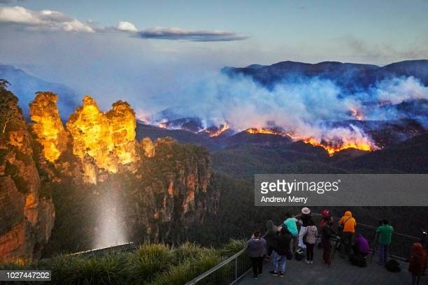 Three Sisters floodlit at dusk, Queen Elizabeth Lookout, viewing platform with tourists watching and photographing fire, bushfire in Jamison Valley, Blue Mountains National Park, Australia