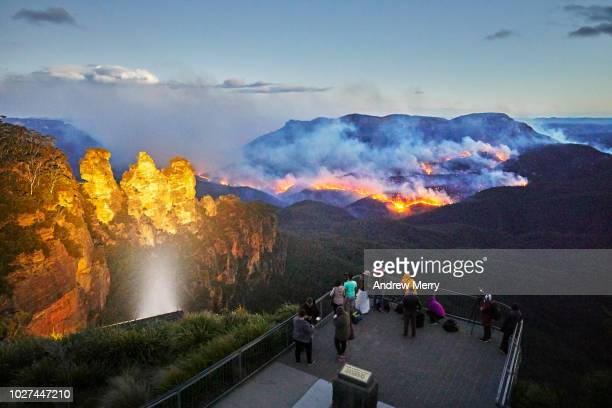 three sisters floodlit at dusk, queen elizabeth lookout, viewing platform with tourists watching and photographing fire, bushfire in jamison valley, blue mountains national park, australia - australian bushfire stock pictures, royalty-free photos & images
