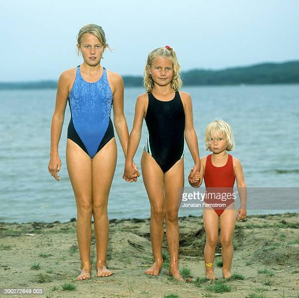 three sisters (4-10) holding hands, standing by lake, portrait - 10 11 years photos stock photos and pictures
