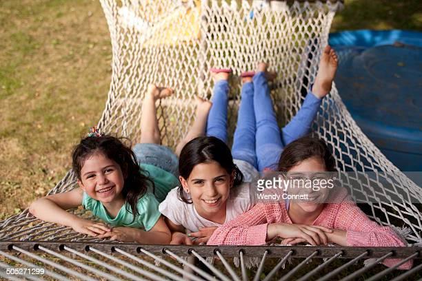 Three sisters lying in hammock