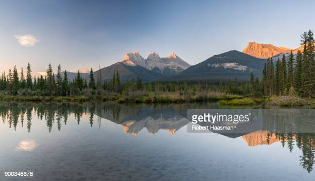 Three Sisters reflecting in calm water, morning atmosphere, Bow River, Canmore, Banff National Park, Alberta, Canada