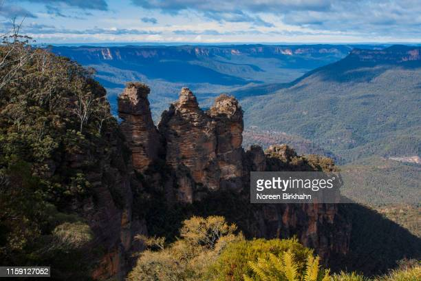 three sisters rock formation from echo point lookout with the blue mountains in background - great dividing range stock-fotos und bilder