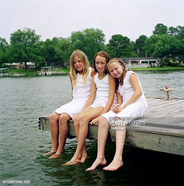Three sisters (10-11, 12-13) sitting on jetty, portrait