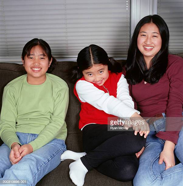 Three sisters (6-7), (12-13), (16-17), sitting on sofa in living room, portrait