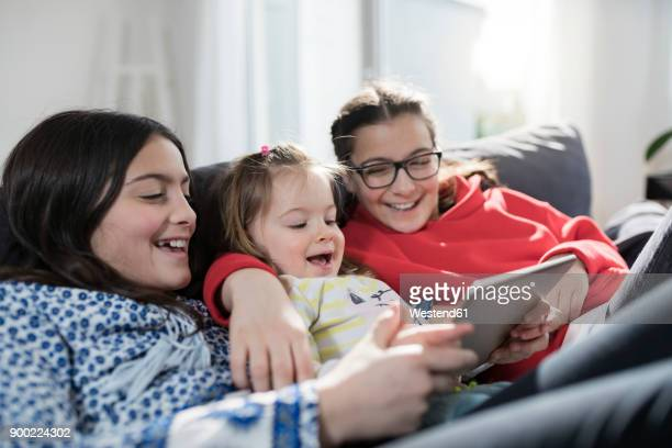 Three sisters smiling and holding tablet on sofa in living room