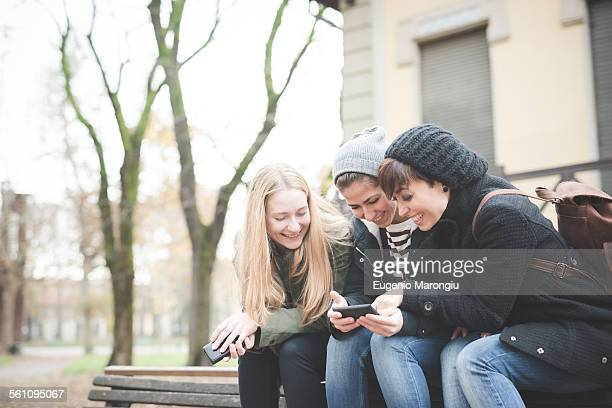 Three sisters using smartphone on park bench